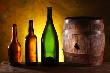 Wooden barrel with colors bottles.