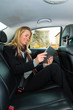 Woman driving in taxi using tablet computer