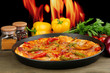 Tasty pepperoni pizza in pan with vegetables on flame