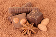 Chocolate sweets with cocoa, on brown background