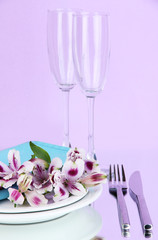 Festive table setting with flowers on lilac background