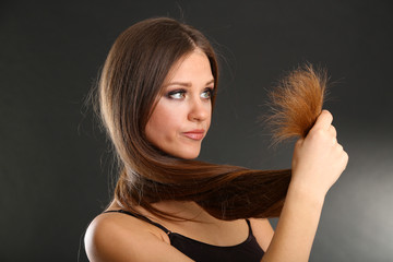 Beautiful woman holding split ends of her long hair,