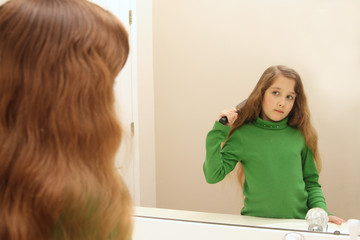 Girl looks at her reflection while getting ready