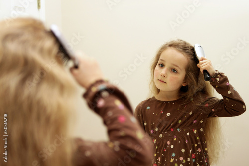 Cute little girl brushing hair while looking in the mirror