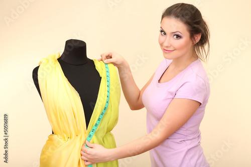 Beautiful young dressmaker in workroom