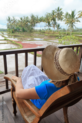 woman on chair overlooking rice fields