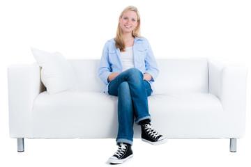 blonde frau sitzt entspannt auf dem sofa