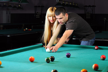 Young couple playing snooker in a billiard club