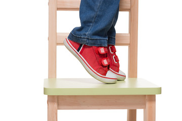 child's feet standing on the little chair on tiptoes