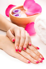 woman's hands with fragrant rose petals and towel. Spa