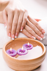 hands with aromatic candles and towel. Spa