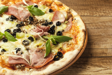 close up of tasty pizza on wooden background