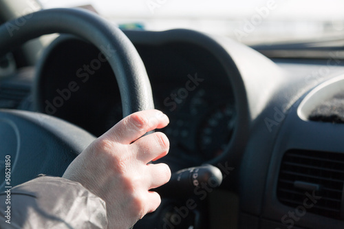 Womans hand on steering wheel of car. Driving woman.