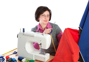 Middle-aged woman holding a pair of scissors at the sewing machi