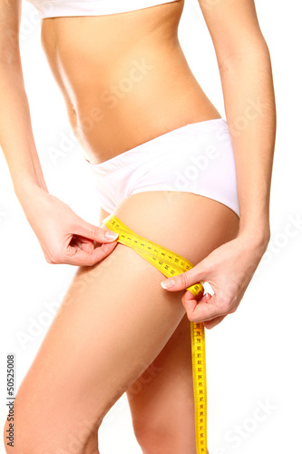 Woman measuring her thigh with a yellow metric tape measure