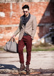 sexy fashion man model dressed elegant holding a bag posing