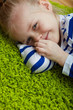 Kid girl lying on green  floor.  isolated portrait.