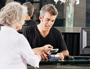 Customer Paying Through Mobile Phone At Salon