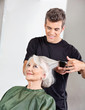 Hairstylist Straightening Senior Woman's Hair