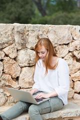 junge frau arbeitet draußen mit laptop