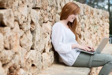 junge frau schreibt draußen am laptop