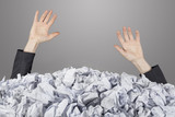 Hands reach out from big heap of crumpled papers