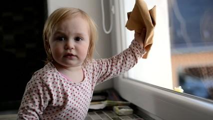 la jeune fille nettoyage la fenêtre