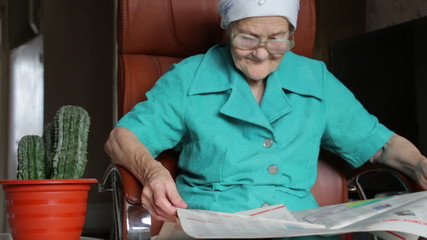 old woman reading and turn over pages of newspaper