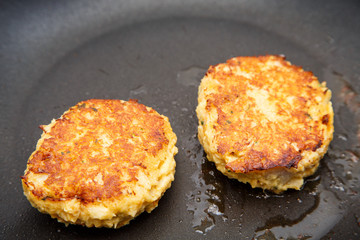 Two Crab Cakes Browning in Saute Pan