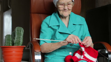 old woman sitting on chair and knitting
