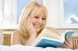 Junge Frau liest Buch im Bett