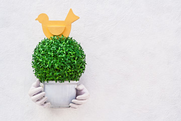 Artificial flora in flowerpot decorated on white wall