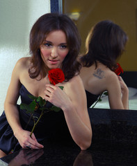 Sexy young woman in black lingerie a red rose
