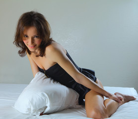 sexy woman on her bed holding a pillow