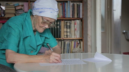 old woman writing letter then take off glasses