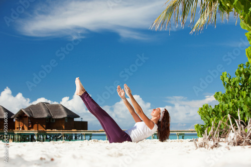 Pretty woman doing yoga exercises on the beach