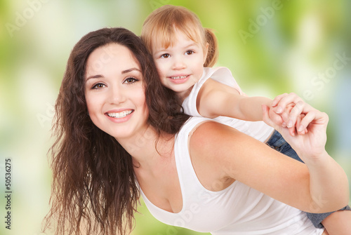 Happy mother and daughter playing on nature background