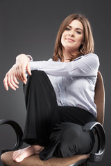 Beautiful business woman sitting in chair