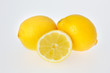 A Cut Lemon in front of Two Lemons