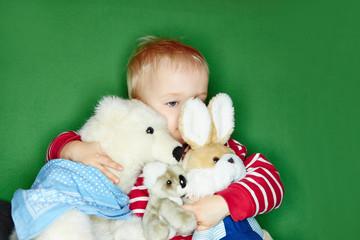 Kind umarmt viele Kuscheltiere
