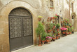 wrought iron gate and many flowers in tuscan village