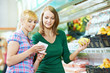 Two women at supermarket fruits shopping