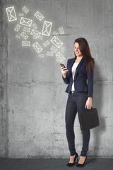 Beautiful businesswoman sending a message on smartphone