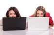 two girls having fun on their laptops