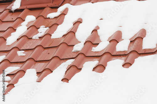 Snow melting on a red roof