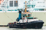 Tugboat pulling a large ship in the Dutch Rotterdam harbor
