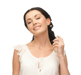 woman spraying pefrume on her neck