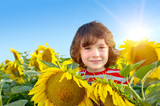 Sweet boy in field with sunflowers