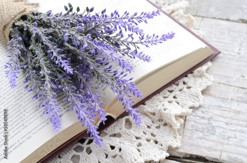 Bunch of lavender laying upon open book on vintage doily