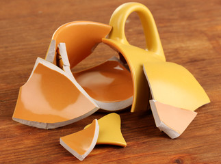 Yellow broken cup on wooden background